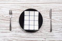 Fondo de madera blanco de la tabla de la placa de la servilleta de la bifurcación de los cubiertos vacíos del cuchillo Foto de archivo
