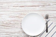 Fondo de madera blanco de la tabla de la placa de la servilleta de los cubiertos vacíos de la bifurcación Fotos de archivo libres de regalías