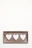 Fondo de madera blanco del vintage con tres corazones Foto de archivo libre de regalías