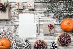 Fondo de madera blanco Tarjeta del invierno Naranjas Pinecone Verde de la rama del abeto Tortas de la fruta Espacio para poner le Imagen de archivo libre de regalías