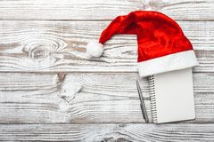 Fondo de madera blanco Tarjeta del invierno Su sombrero del ` s de Papá Noel Letra para tarjeta de felicitación de la Navidad o d Fotografía de archivo libre de regalías