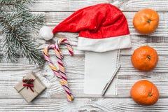 Fondo de madera blanco Tarjeta de felicitación del invierno Verde del abeto Naranjas Regalo Caramelos coloreados Espacio para pon Foto de archivo libre de regalías