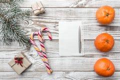Fondo de madera blanco Tarjeta de felicitación del invierno Verde del abeto Naranjas Regalo Caramelos coloreados Espacio para pon Fotos de archivo libres de regalías