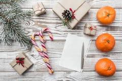 Fondo de madera blanco Tarjeta de felicitación del invierno Verde del abeto Naranjas Regalos Caramelos coloridos Espacio para pon Fotografía de archivo libre de regalías