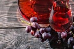 Fondo de madera con el vidrio de vino rojo y un manojo de uvas Fotos de archivo libres de regalías