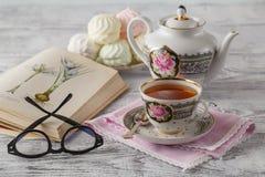 Fondo de madera con la taza de té y un libro encendido cerca de una cucharilla Foto de archivo