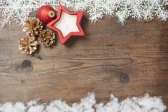Fondo de madera con las decoraciones de la nieve y de la Navidad del invierno encendido Foto de archivo
