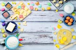 Fondo de madera con las galletas y los ingredientes de Sugar Easter para los vagos Foto de archivo