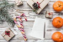 Fondo de madera con los copos de nieve Tarjeta de felicitación del invierno Verde del abeto Naranjas Regalos Caramelos coloridos Imagen de archivo libre de regalías