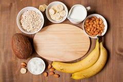 Fondo de madera con los ingredientes y dos porciones de smoothies Imagen de archivo libre de regalías