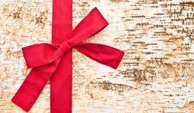 Fondo de madera con un arco rojo Foto de archivo libre de regalías