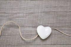 Fondo de madera con un corazón blanco. imagen de archivo