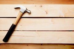Fondo de madera con un martillo Imagen de archivo libre de regalías