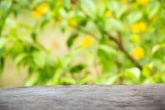 Fondo de madera contra el contexto de flores de color verde amarillo brillantes Poco campo de la profundidad, empañando, efecto d Fotografía de archivo