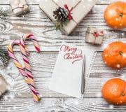 Fondo de madera Copos de nieve Tarjeta de felicitación del invierno Verde del abeto Naranjas Regalos Caramelos coloridos Espacio  Fotografía de archivo