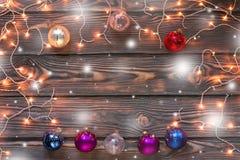 Fondo de madera de la Navidad con las luces, la nieve y los ornamentos Fotografía de archivo