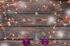 Fondo de madera de la Navidad con las luces, la nieve y los ornamentos Fotos de archivo