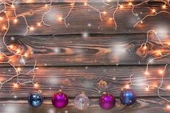 Fondo de madera de la Navidad con las luces, la nieve y los ornamentos Imagen de archivo libre de regalías