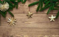 Fondo de madera de la Navidad con las ramas de las decoraciones del árbol y de la paja de abeto, espacio vacío Fotos de archivo libres de regalías