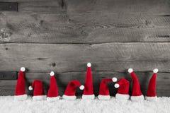 Fondo de madera de la Navidad con los sombreros rojos de santa para un franco festivo Imagenes de archivo