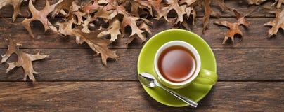Fondo de madera de la taza de té de las hojas Imagen de archivo libre de regalías