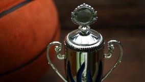 Fondo de madera del escritorio de la taza del oro de la bola del baloncesto