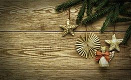 Fondo de madera del vintage de la Navidad con las ramas de las decoraciones del árbol y de la paja de abeto Imagen de archivo