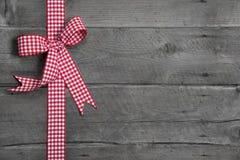 Fondo de madera gris con el arco a cuadros rojo y blanco como borde Fotos de archivo libres de regalías