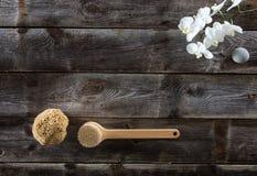 Fondo de madera rústico con el cepillo, la esponja natural y las orquídeas blancas Imagen de archivo