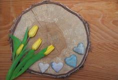Fondo de madera rústico con la rebanada del árbol, los tulipanes y el corazón de piedra Fotos de archivo