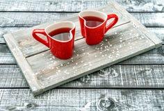 Fondo de madera rústico de la bebida roja en forma de corazón de las tazas foto de archivo