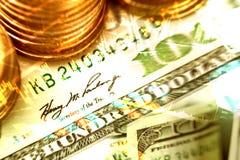 Fondo de monedas y de dólares de billete de banco con el gráfico del mercado de acción Imagen de archivo