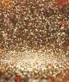 Fondo de oro abstracto del brillo con el confeti anaranjado, Celebra Foto de archivo libre de regalías
