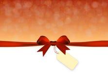 Fondo de oro y rojo brillante con el arco rojo con la etiqueta Imágenes de archivo libres de regalías