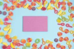 Fondo de papel azul con las jaleas azucaradas y la libreta en blanco fotografía de archivo