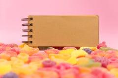 Fondo de papel rosado con las jaleas azucaradas y la libreta en blanco fotografía de archivo