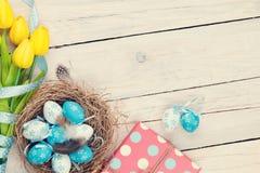 Fondo de Pascua con los huevos azules y blancos en la jerarquía, tulipán amarillo Fotos de archivo libres de regalías