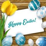Fondo de Pascua con los huevos coloreados, los tulipanes amarillos y la tarjeta de felicitación sobre la madera blanca Fotografía de archivo libre de regalías