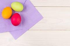 Fondo de Pascua con los huevos de Pascua Huevos de Pascua coloridos con el pur Fotografía de archivo libre de regalías
