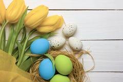 Fondo de Pascua con los huevos coloridos en jerarquía y los tulipanes amarillos sobre la madera blanca Visión superior con el esp foto de archivo libre de regalías