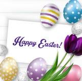 Fondo de Pascua con los huevos coloridos, los tulipanes púrpuras y la tarjeta de felicitación sobre la madera blanca Foto de archivo