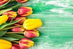 Fondo de Pascua con los huevos coloridos y los tulipanes amarillos sobre la madera imagen de archivo