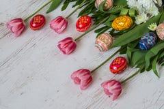 Fondo de Pascua con los huevos de Pascua y los tulipanes rosados en fondo de madera ligero Imagen de archivo