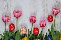 Fondo de Pascua con los huevos de Pascua y los tulipanes rosados en fondo de madera ligero Foto de archivo libre de regalías