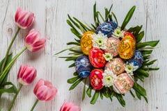 Fondo de Pascua con los huevos de Pascua y los tulipanes rosados en fondo de madera ligero centro de flores bajo la forma de jera Foto de archivo