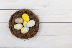 Fondo de Pascua con los huevos en jerarquía sobre la madera blanca Visión superior con el espacio de la copia imagen de archivo libre de regalías