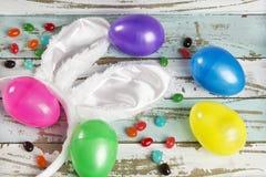 Fondo de Pascua con los huevos, los oídos del conejito y las habas de jalea Foto de archivo libre de regalías