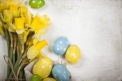 Fondo de Pascua con los huevos pintados y los narcisos florecientes Imagen de archivo libre de regalías