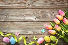 Fondo de Pascua con los huevos y los tulipanes coloridos de la primavera Foto de archivo