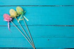 Fondo de Pascua Huevos de Pascua adornados multicolores, polvo multicolor en un fondo de la turquesa Espacio libre Foto de archivo
